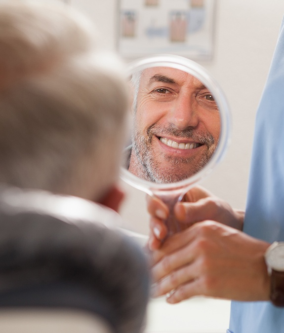 man smiling into circle mirror