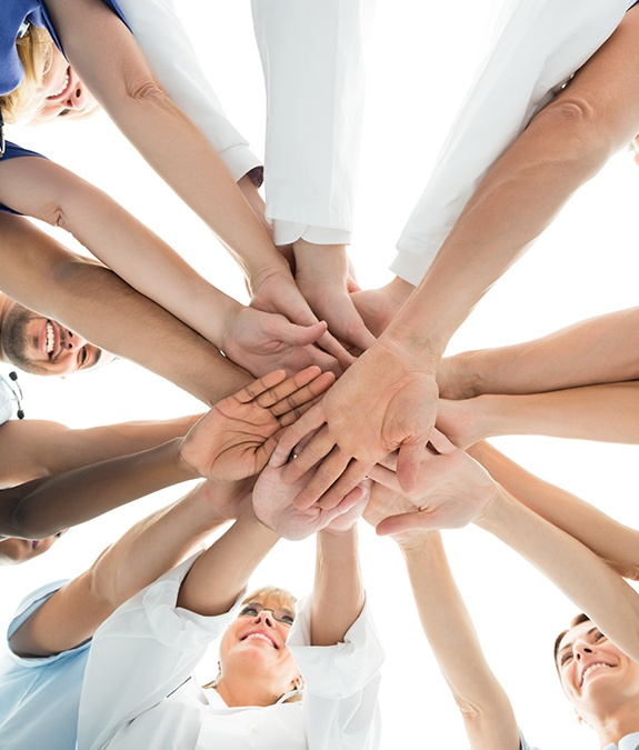 group of people putting hands into middle of circle