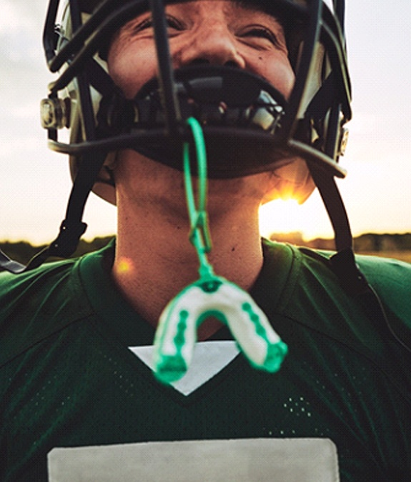 A male football player wearing sports equipment and a custom mouthguard