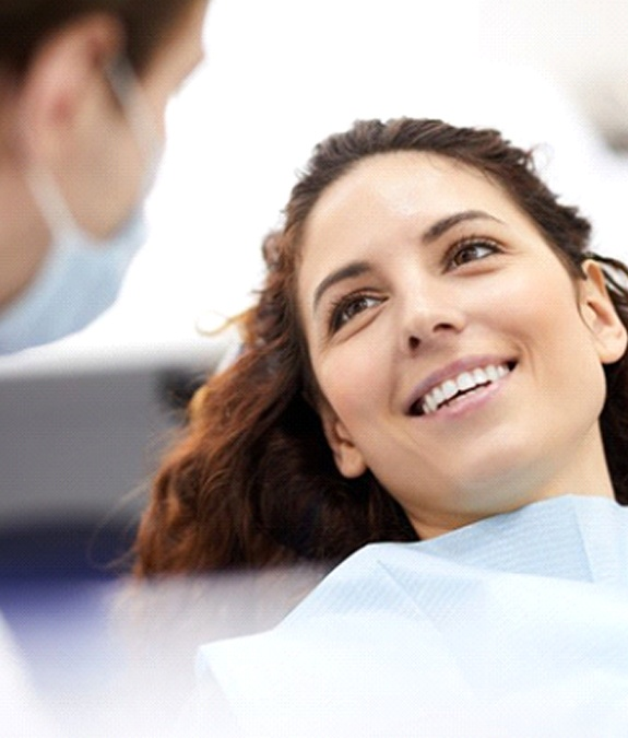 Woman with brown hair smiling in dental chair
