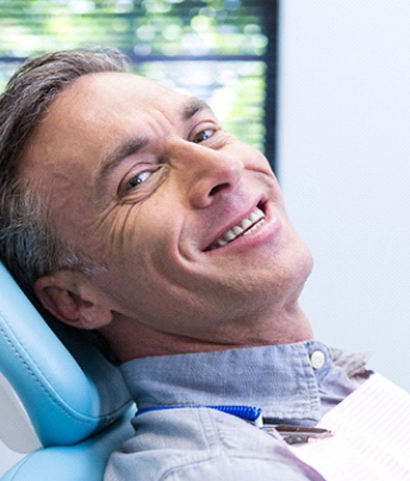 Man in blue shirt smiling in dental chair