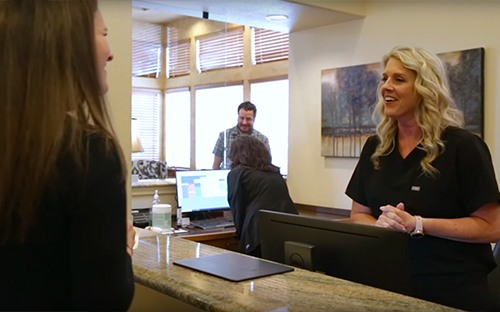mother holding daughter and smiling at front desk worker