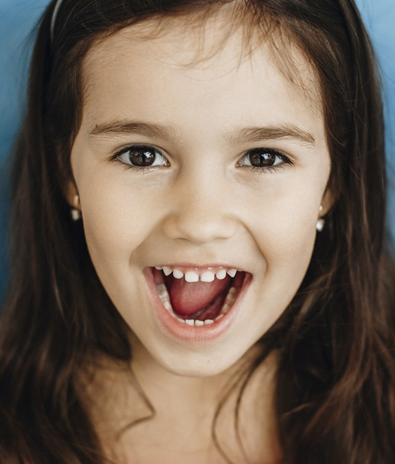 A little girl with long, dark hair smiling with her mouth open to show off her healthy set of teeth