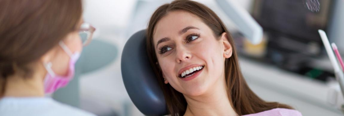 woman smiling at dentist in blue exam chair