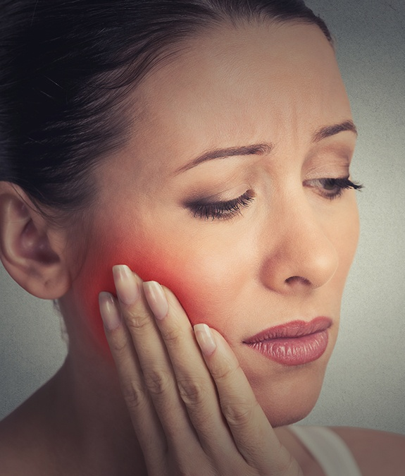 Woman holding cheek in pain before gum disease treatment