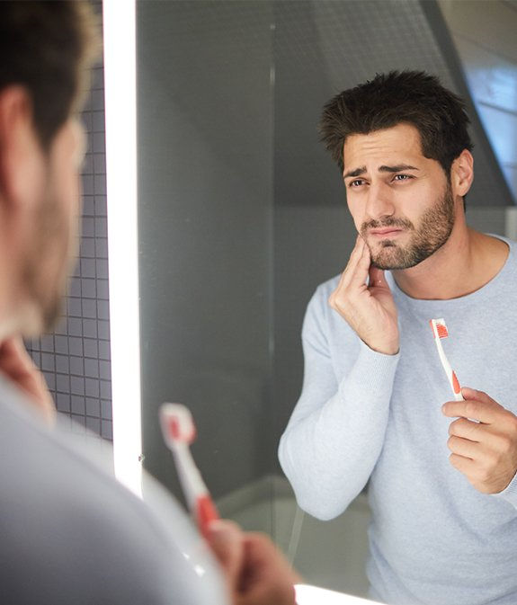 man looking in pain while looking in mirror
