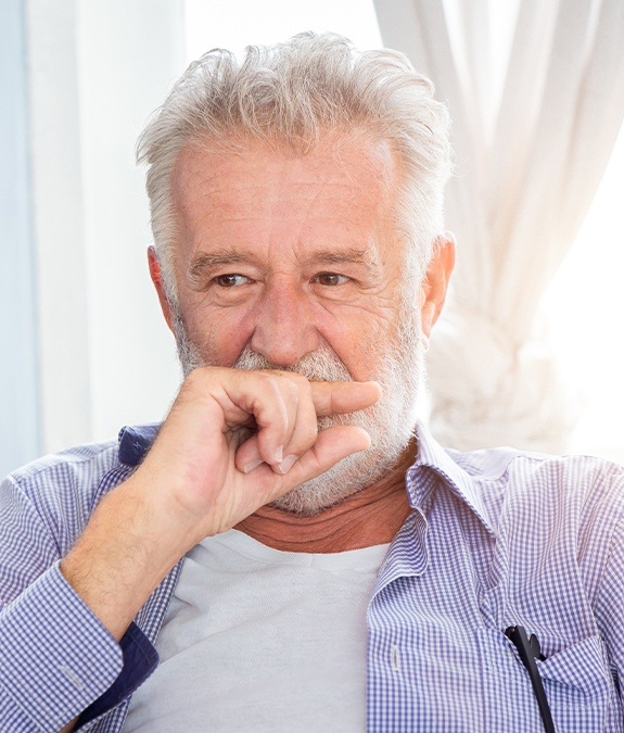 Older man in need of periodontal therapy covering his mouth