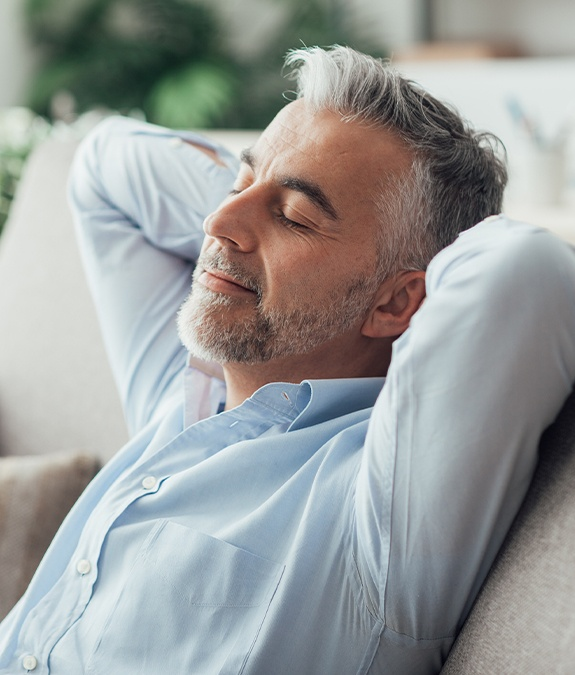 man leaning back and relaxing with hands behind head after sedation dentistry visit
