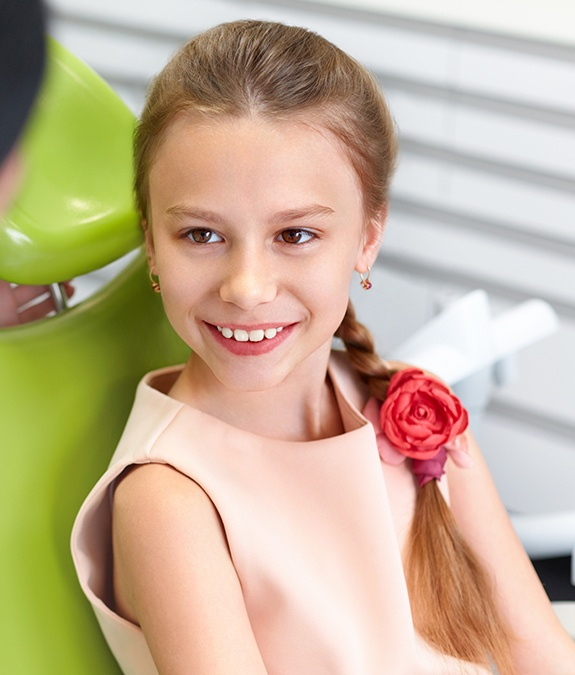 young girl with flower in hair smiling during sedation dentistry visit