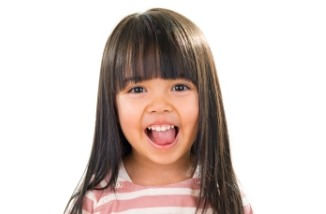 Young girl with bangs looking excited after children's dentistry appointment