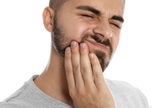 man with beard in need of emergency dentistry holding jaw in pain
